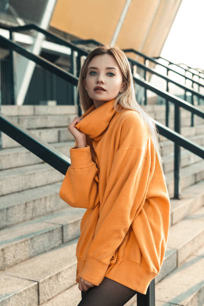 Outdoor fashion portrait of glamour sensual young stylish lady wearing trendy fall outfit , orange sweater, black panty hoses and black boots. Cold season. Warm clothes. Blonde woman with blue eyes stock photo