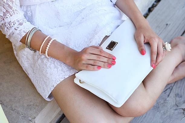 outdoor-mode junge frau halten weiße clutch-handtasche - armband vintage stock-fotos und bilder
