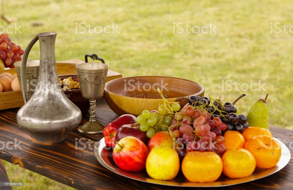 Outdoor feast of fruit with pewter wine goblet and jug. royalty-free stock photo