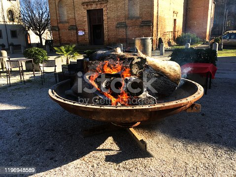 Large  Outdoor Fire in a Metal Bowl in a Square in ia Small town in Italy
