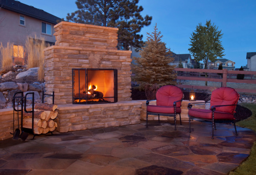 A backyard patio features a fireplace and casual furnishings.  The outdoor fireplace burns with a bright orange glow and is covered by a metal grate.  There is extra wood stored to the left of the stone fireplace in a black unit.  There are two metal chairs with red cushions placed on the flagstone patio.