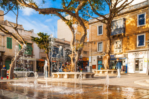 Outdoor fountain on one of streets in Sliema. Winter sunset light. stock photo