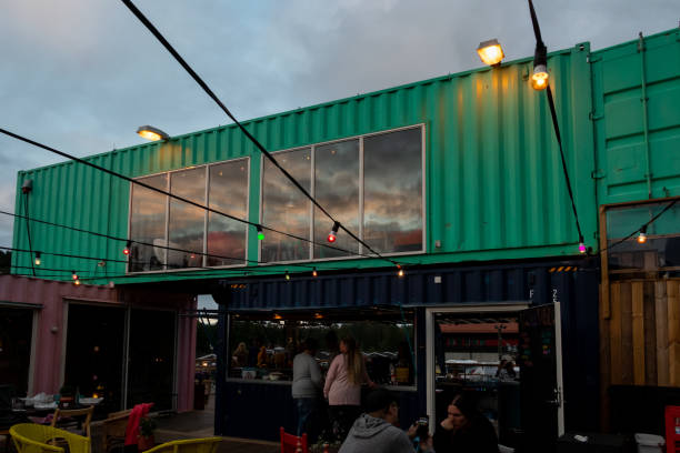 Outdoor front facade night view of  a container pop-up restaurant with windows and a bar with people in Ullared Sweden. stock photo