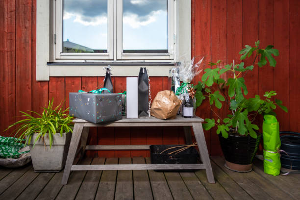 Outdoor front view of a gift present table bench with plants on a porch against red wooden plank wall and a window. stock photo
