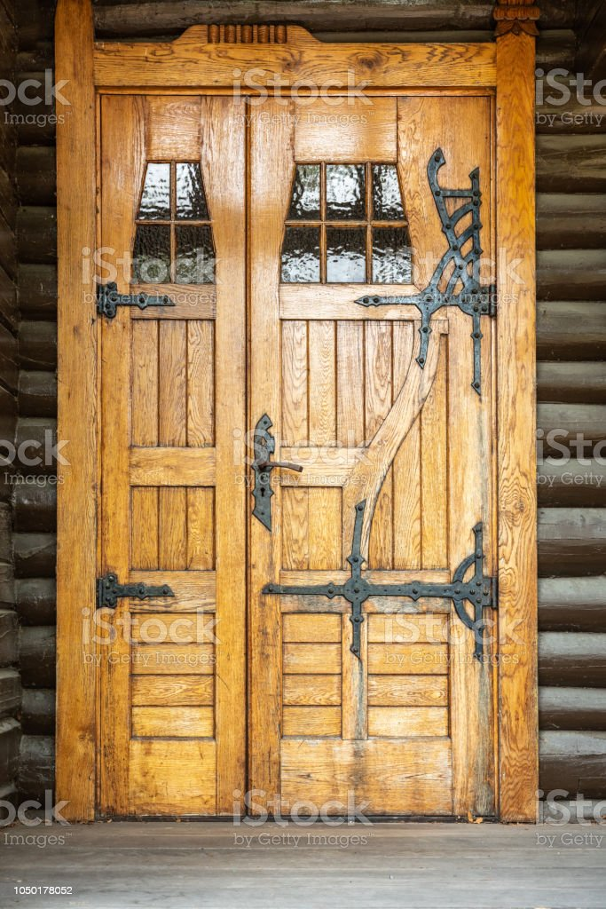 Outdoor front view of a naturally wood finished door entrance. Rustic traditional decorative pattern with iron fittings. stock photo