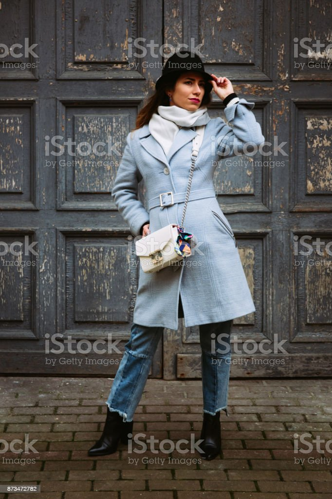 Outdoor full body portrait of young beautiful fashion girl posing on street. Model looking aside. Lady wearing stylish winter clothes. Female fashion. Toned stock photo