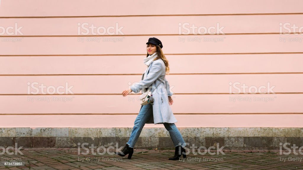 Outdoor full body portrait of young beautiful happy smiling girl walking toward a wall on street. Model looking at camera. Lady wearing stylish winter clothes. Female fashion. stock photo