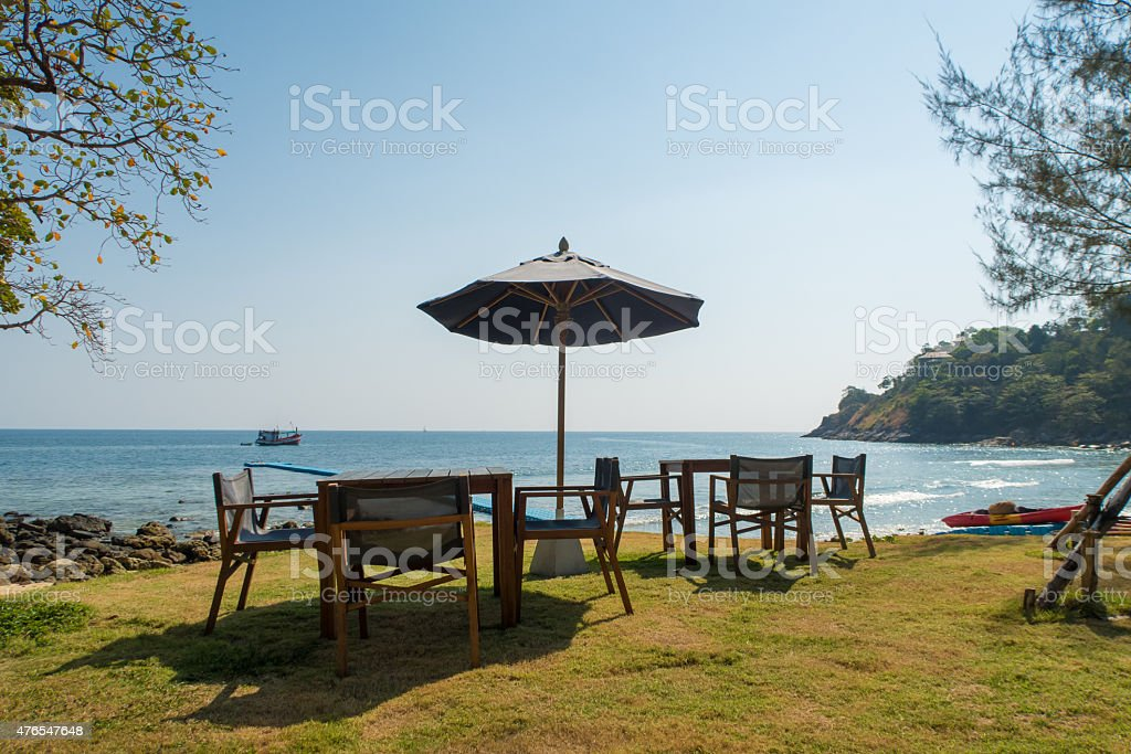 wooden tables and chairs settle in backyard by the sea