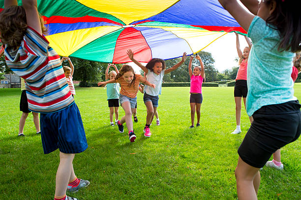 Outdoor Games Children playing a game with a colourful Parachute leisure games stock pictures, royalty-free photos & images