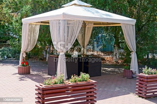 open gazebo with curtains and furniture on the sidewalk in the park among green trees