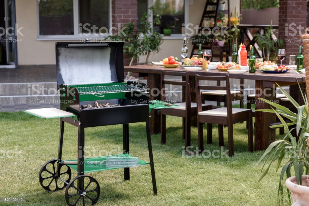 Outdoor grill with coals standing on green lawn and served table with dishes and drinks behind stock photo