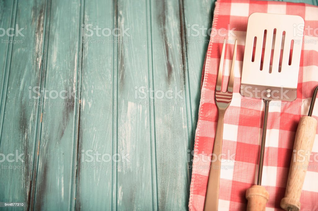 Outdoor grilling, BBQ utensils on rustic picnic table. stock photo
