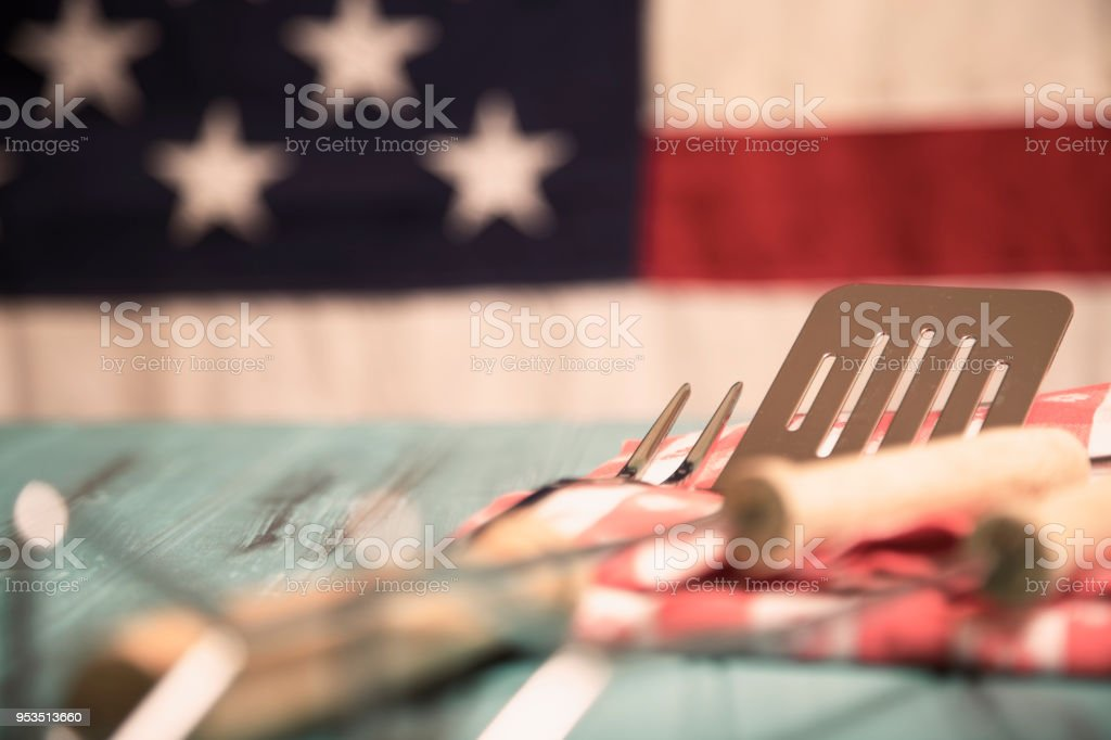 Outdoor grilling, BBQ utensils on rustic picnic table with USA flag. stock photo