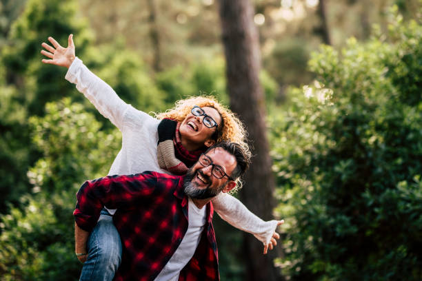 Outdoor happy and cheerful caucasian couple with glasses have fun and enjoy the nature and leisure activity together - man carry woman and both laugh a lot stock photo