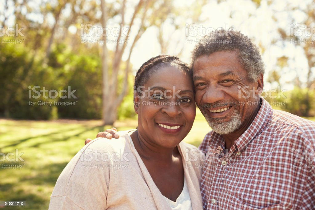 Outdoor Head And Shoulders Portrait Of Mature Couple In Park stock photo