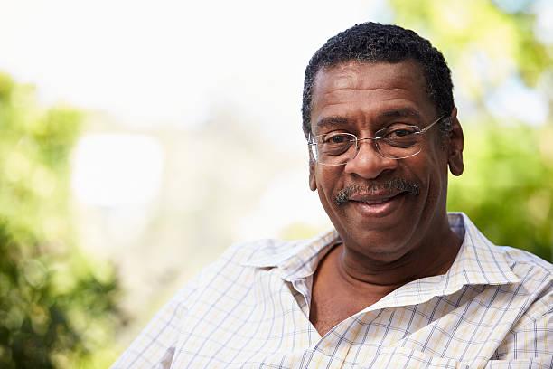outdoor head and shoulders portrait of senior man - senior mann porträts stock-fotos und bilder
