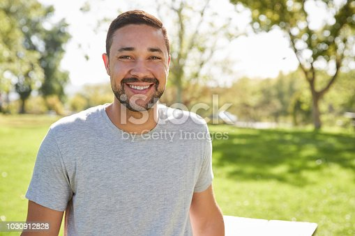 Outdoor Head And Shoulders Portrait Of Smiling Man In Park