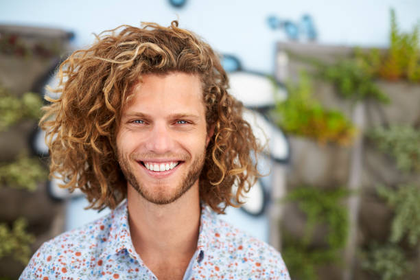 Outdoor Head And Shoulders Portrait Of Smiling Young Man Outdoor Head And Shoulders Portrait Of Smiling Young Man long hair stock pictures, royalty-free photos & images