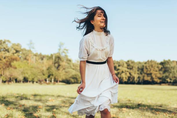 rüzgarlı saçlı güzel mutlu kadın açık hava sıcak hava zevk, doğa arka planda beyaz elbise giyiyor. neşeli kadın güneşli bir günde parkta yürürken gülümsüyor. - beyaz elbise stok fotoğraflar ve resimler