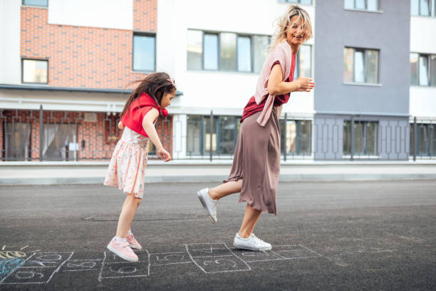 Outdoor image of happy little girl playing hopscotch with her mother on playground outdoors. Child plays with her mom outside. Kid plays hopscotch drawn on pavement. Activities and games for children stock photo