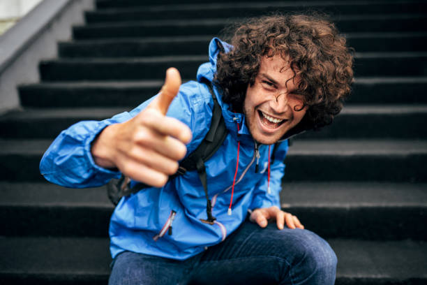 Outdoor image of smiling young man with curly hair sitting on stairs of a building with backpack, showing thumb up. Attractive male resting in the street on a rainy day. Hipster guy shows good gesture stock photo