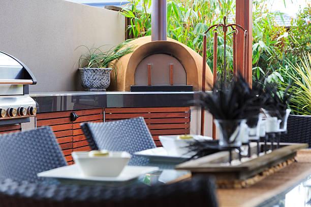 Outdoor-Küche mit Edelstahl-Barbecue und Pizza-Ofen – Foto