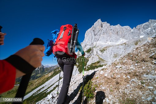 rear view female hiker woman with backpack and tripot hiking up steep mountain in austrian alps on sunny autumn day with clear blue sky followed by another hiker