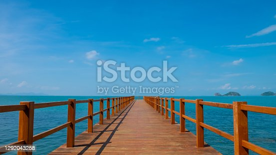 Outdoor, landscape shot of wooden walk way into the middle of the ocean. With clear blue sky and cloud with seascape island view. Tropical travel destination ideal for background with copy space.
