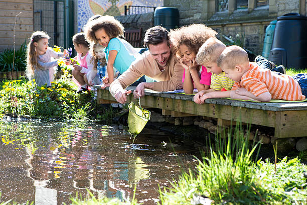 Outdoor Lesson On Pond Life Children enjoying an outdoors lesson on nature with their teacher. He holds a net above the pond water which the children are fascinated by. Some of the children are holding flowers which they have picked. field trip stock pictures, royalty-free photos & images