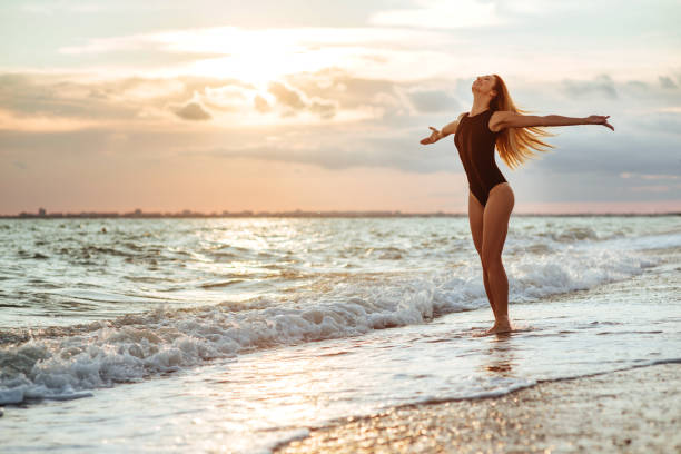 Outdoor lifestyle portrait of beautiful girl in black swimsuit stock photo