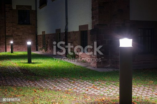 istock Outdoor lights (lanterns, bollards) in front of an old administration building illuminating a walkway in the garden at night 921916714