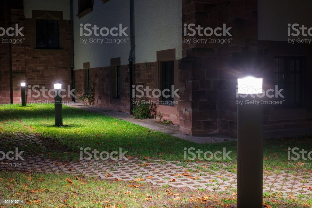 Outdoor lights (lanterns, bollards) in front of an old administration building illuminating a walkway in the garden at night stock photo