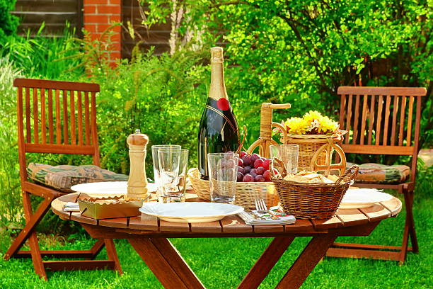 outdoor lunch table with bottle of wine on the backyard - gästekorb stock-fotos und bilder