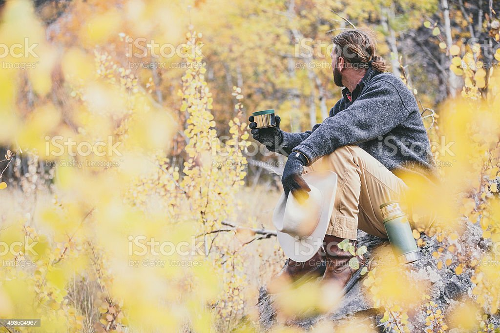 Outdoor man sitting on rock in the woods of Montana stock photo