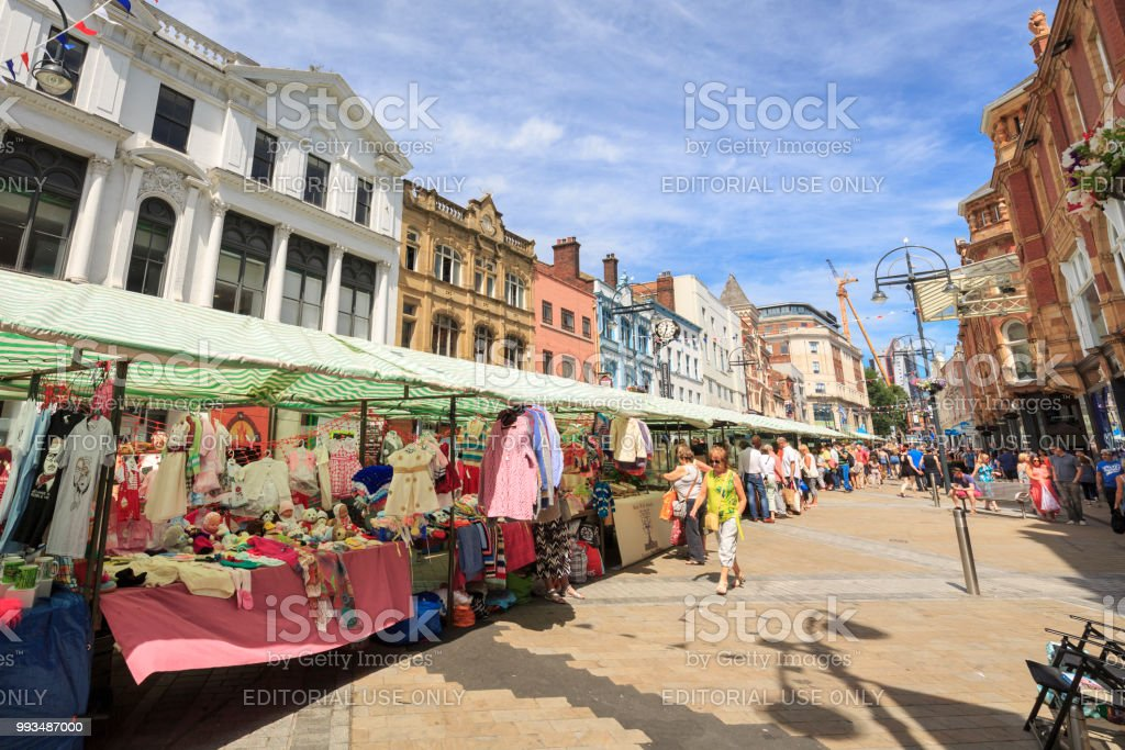 Outdoor market and shoppers walking in a pedestrianised area of Leeds stock photo