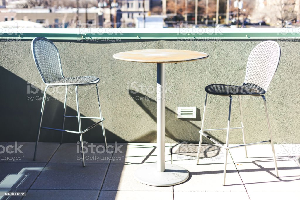 Outdoor Metal Bistro Table and Chairs on Balcony in Urban Western USA Urban Western USA Outdoor Metal Bistro Table and Chairs (Shot with Canon 5DS 50.6mp photos professionally retouched - Lightroom / Photoshop - original size 5792 x 8688 downsampled as needed for clarity and select focus used for dramatic effect) Balcony Stock Photo
