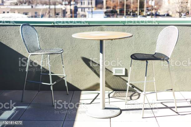 Outdoor Metal Bistro Table And Chairs On Balcony In Urban Western Usa Stock Photo - Download Image Now