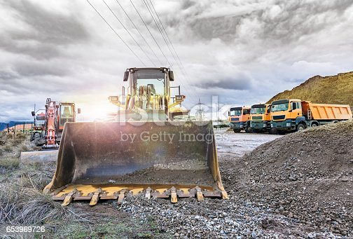 istock Outdoor mine with heavy machinery, earthmoving and rock excavators 653969726