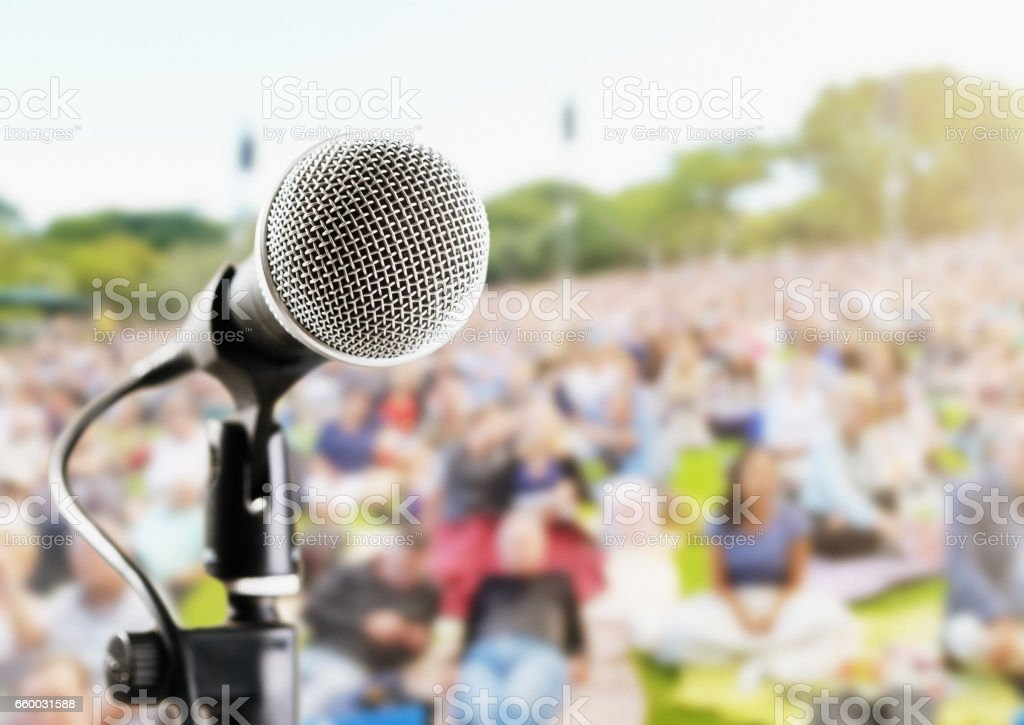 Outdoor music festival or concert: microphone with defocused audience stock photo