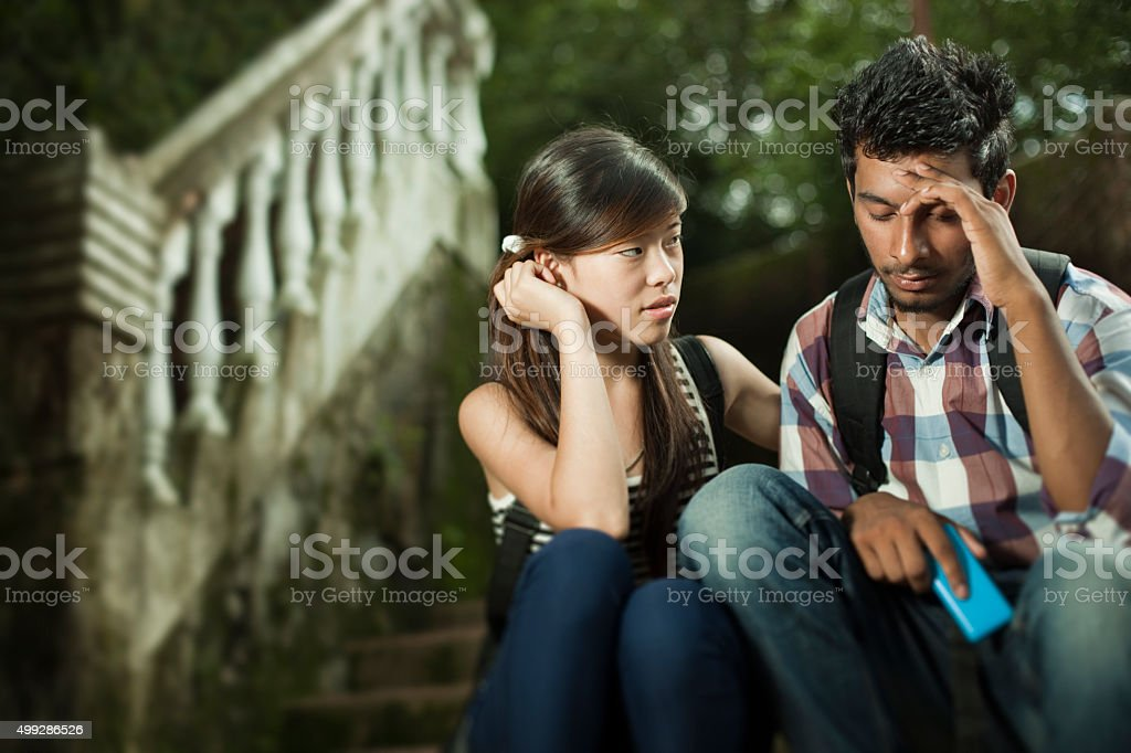 Outdoor on stairs girl consoling to sad boy in campus. stock photo
