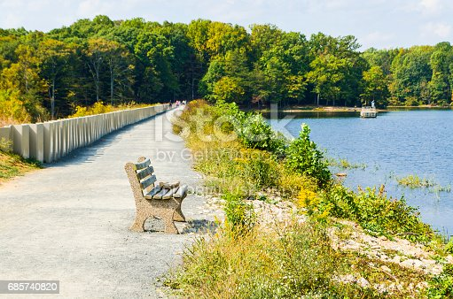 istock Outdoor park with bench and sidewalk on dam with people walking in Virginia during autumn 685740820