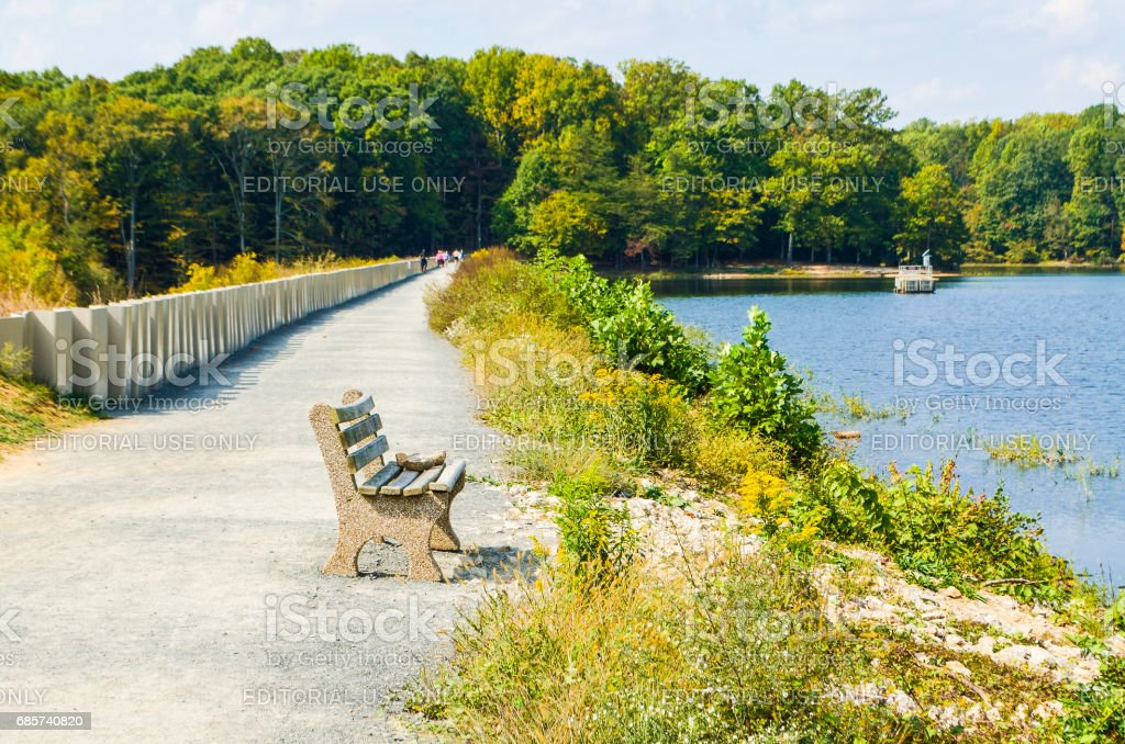 Outdoor park with bench and sidewalk on dam with people walking in Virginia during autumn stock photo