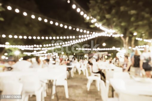 Outdoor party blurry night image background for holiday festival with beautiful bokeh light in vintage style.