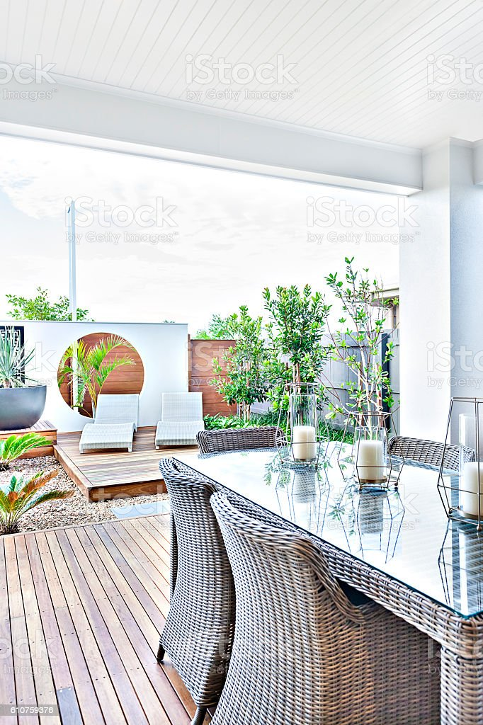 Outdoor patio area with rattan chairs on the wooden floor stock photo