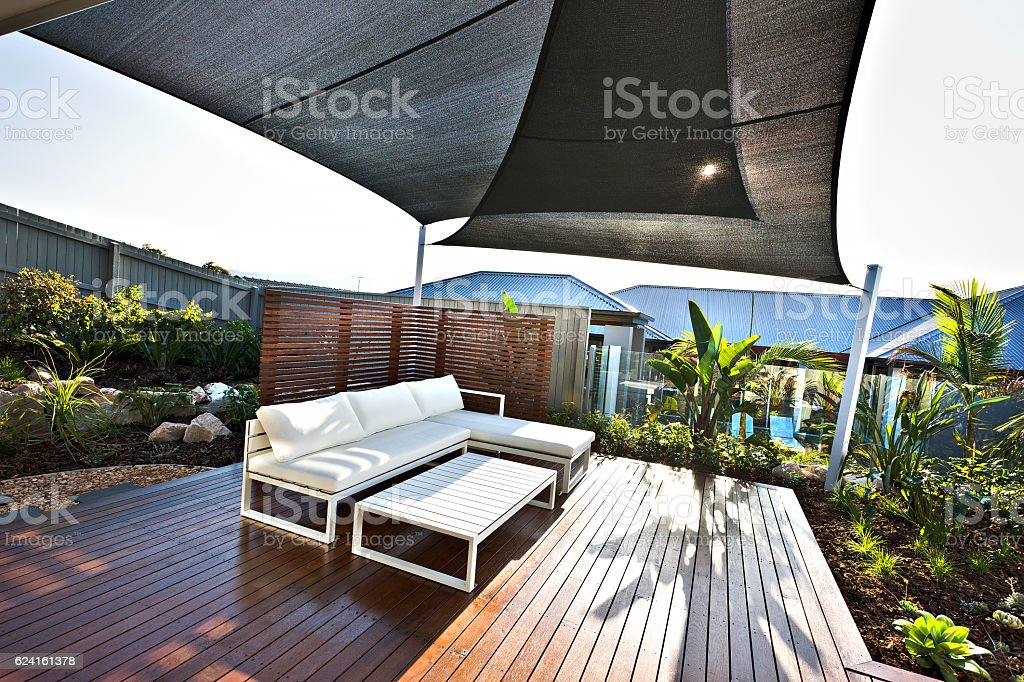 Outdoor patio area with white benches and wooden floor stock photo