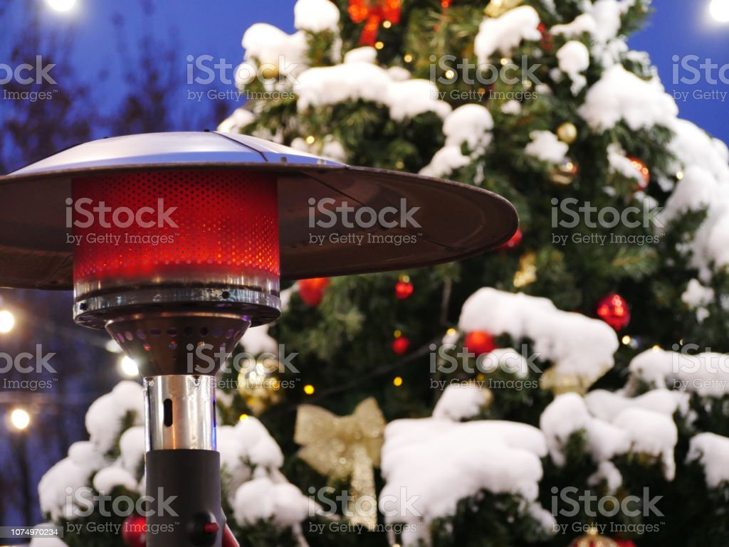 Close up view of an outdoor patio heater in front of the Christmas...