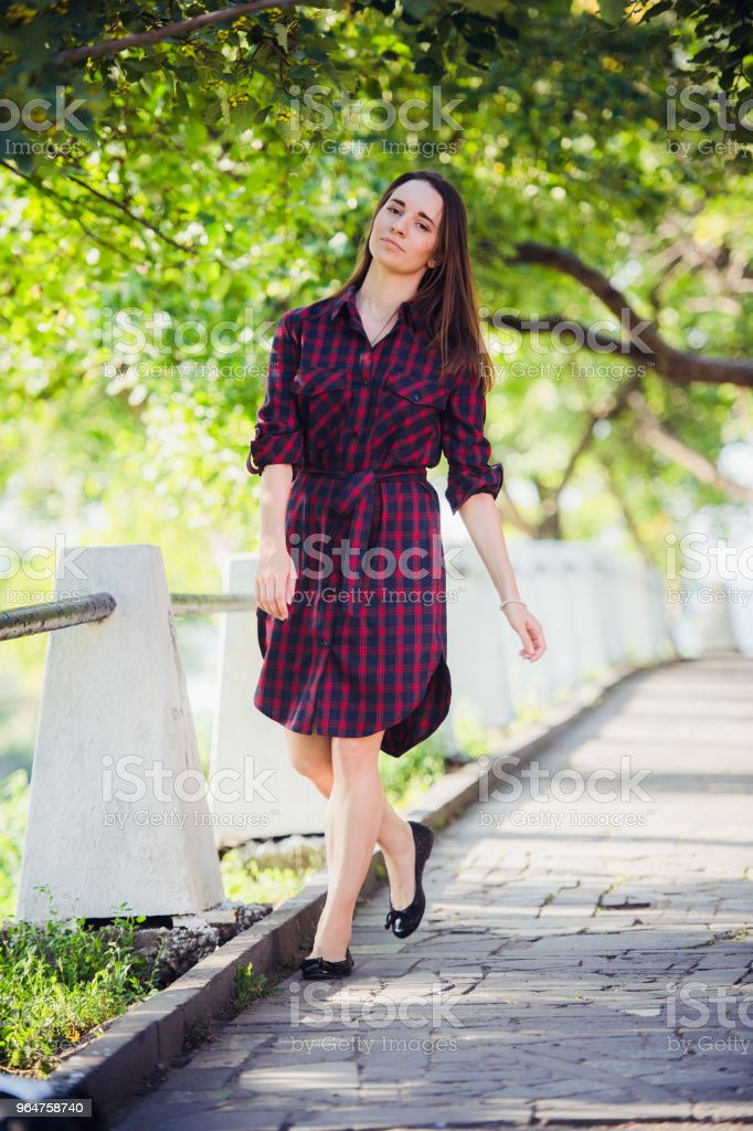 Outdoor photo of beautiful young women standing in a park, with violet colored clothing royalty-free stock photo