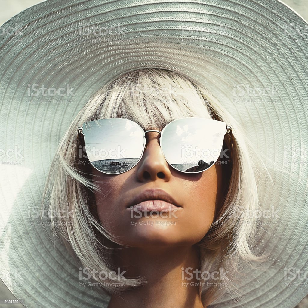 Outdoor photo of young lady in hat and sunglasses stock photo