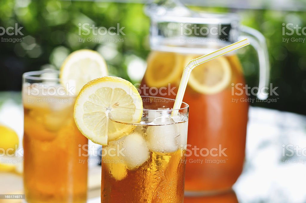Outdoor picnic table set with pitcher and glasses of ice tea stock photo