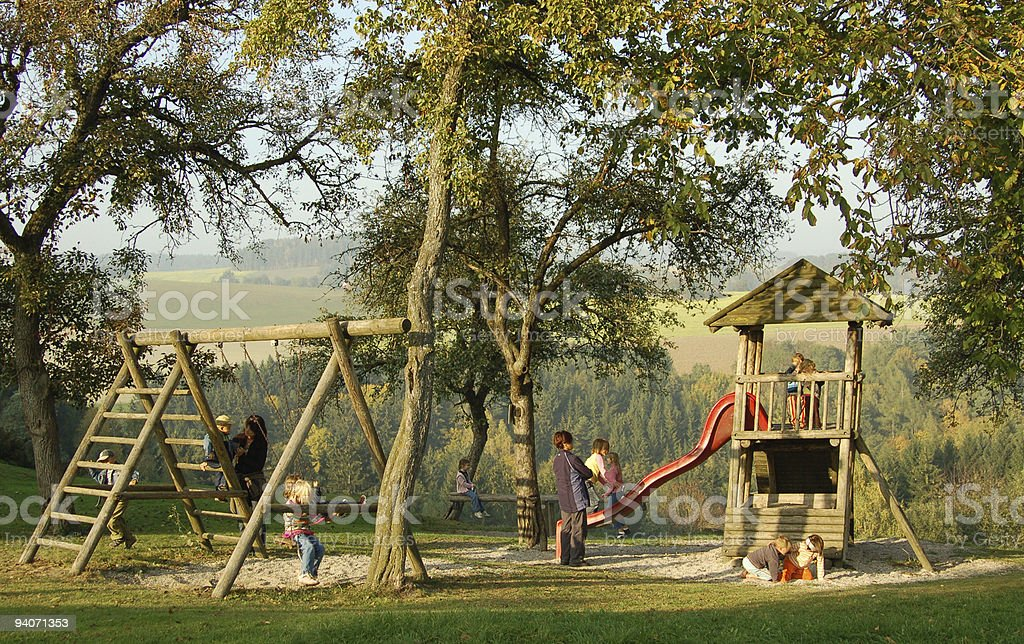 Outdoor play equipment with trees, grass and sand stock photo